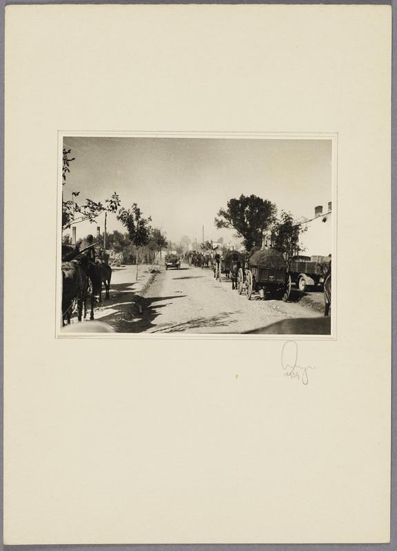 Wehrmachtssoldaten mit Pferdefuhrwerken in einer zerstörten Ortschaft, recto