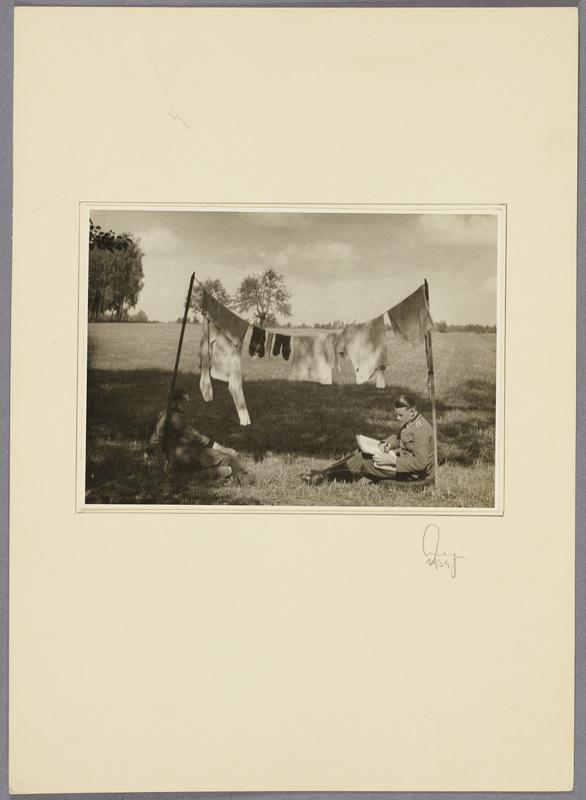 Zwei Soldaten sitzen unter hängender Wäsche auf einem Feld, recto