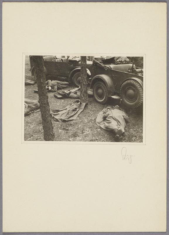 Soldaten schlafen auf dem Boden vor zwei Militärfahrzeugen, recto