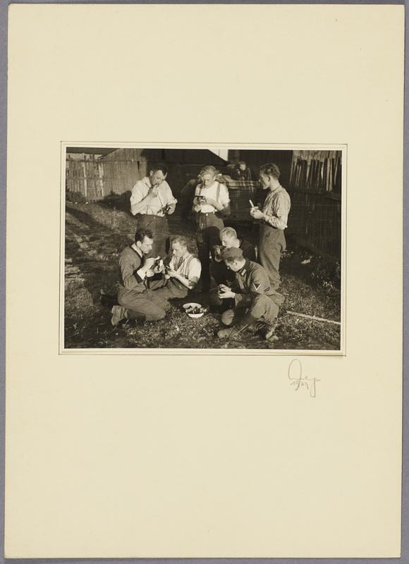 Kurt Seeliger (h. l.) und sechs Wehrmachtssoldaten beim Essen im Freien, recto