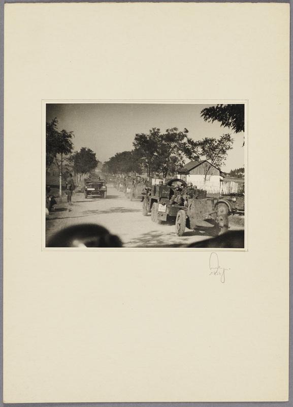 Militärfahrzeuge fahren mit Panzerabwehrkanonen auf einer Landstraße, recto