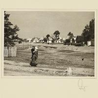 Eine polnische Frau steht mit einem Kind auf dem Arm vor einem Dorf