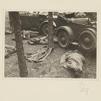Soldaten schlafen auf dem Boden vor zwei Militärfahrzeugen