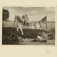 Zwei Soldaten sitzen unter hängender Wäsche auf einem Feld