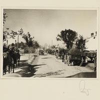 Wehrmachtssoldaten mit Pferdefuhrwerken in einer zerstörten Ortschaft