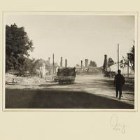Deutsche Militärfahrzeuge fahren durch eine zerstörte Ortschaft
